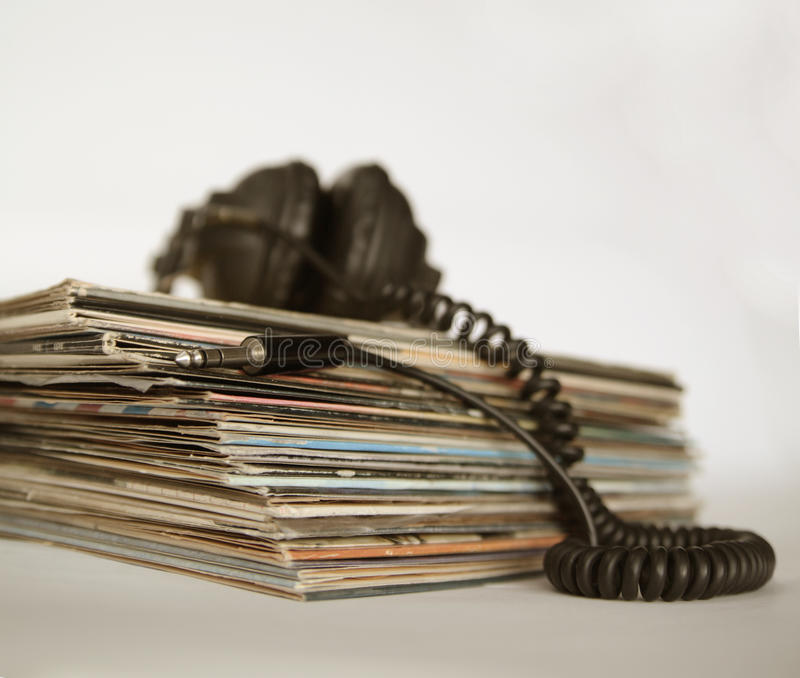 Sepia-style photo of vinyl records and vintage headphones. Dingy sepia-style photo of vinyl records and vintage headphones stock images