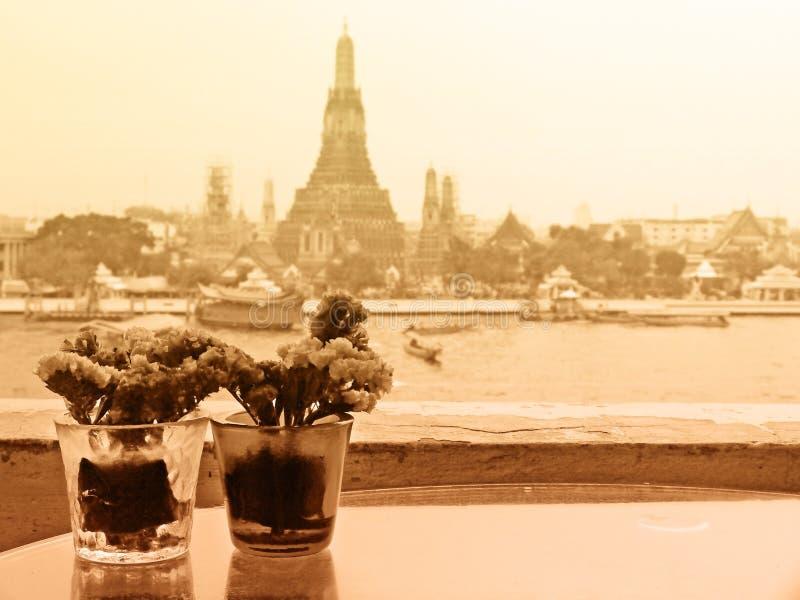 Sepia Tone Couple Vases de flores con Temple of Dawn en fondo con el color suave del foco filtrado usado como plantilla imagen de archivo