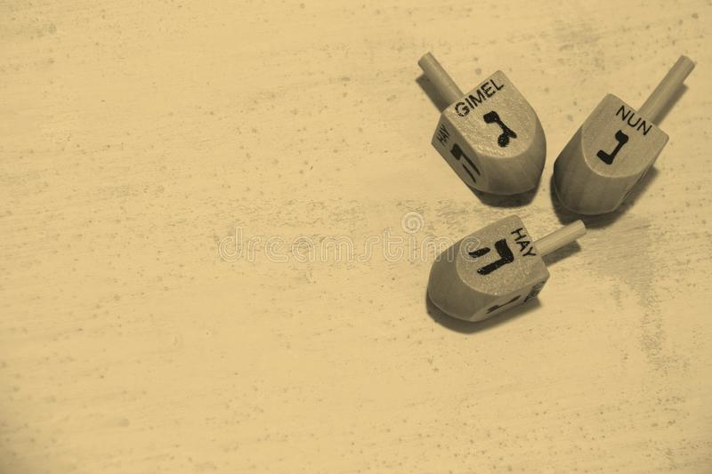 Sepia Toned Image of Wooden dreidels for hanukkah over grunge backgro royalty free stock image