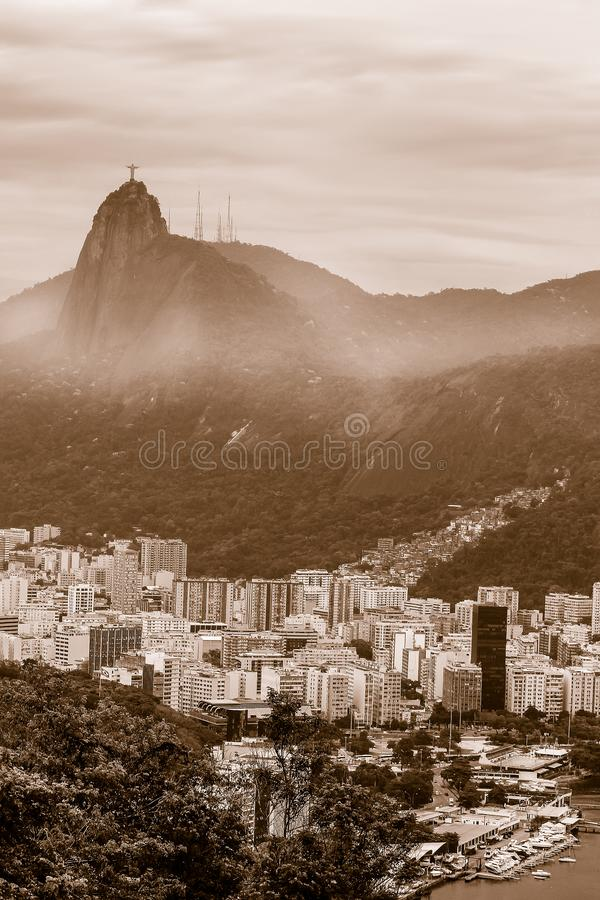 Sepia toned View of city Rio de Janeiro with Favelas in the Hills with misty statue on Mountain stock fotografie