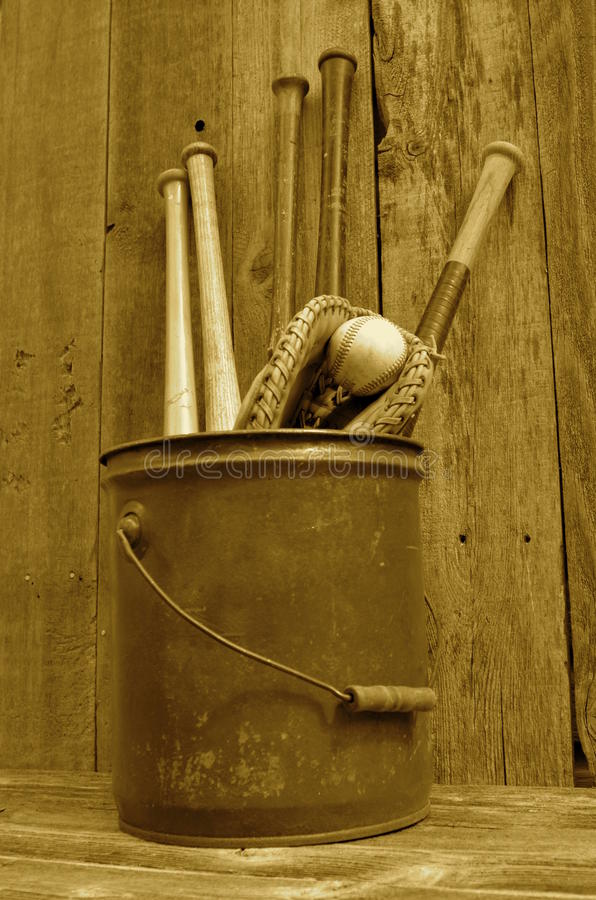 (Sepia) Vintage baseball wood bat, glove, and ball in pail. Old vintage baseball bats glove and ball are stored in a five gallon pail royalty free stock photo