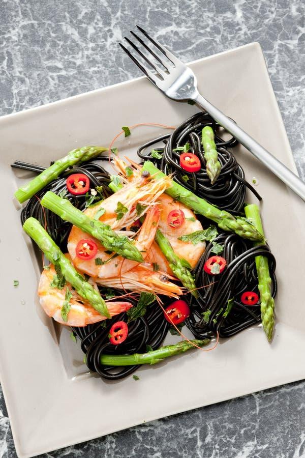 Sepiaspaghettis mit Garnelen, Spargel und Paprikas lizenzfreies stockbild