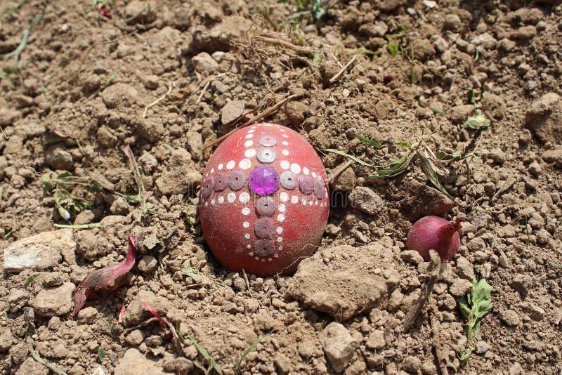 Seppellendo il vecchio uovo di Pasqua nel primo solco della terra, campo immagini stock libere da diritti