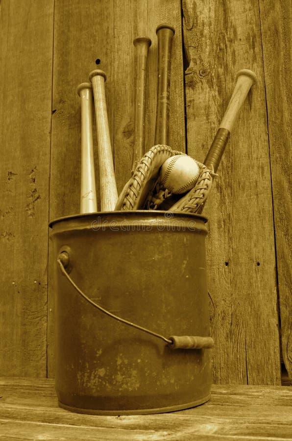(Seppia) pipistrello di legno, guanto e palla di baseball d'annata in secchio fotografia stock libera da diritti