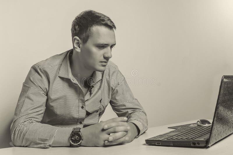 Seppia tonificata L'uomo d'affari serio con le mani ha afferrato l'esame del computer portatile in ufficio fotografia stock libera da diritti