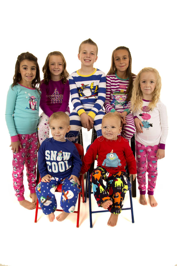 Sept beaux enfants en bas âge portant le sourire de pyjamas d'hiver images stock
