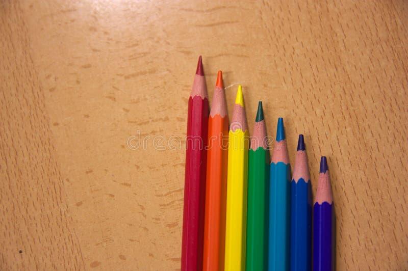 Sept crayons au-dessus d'une table photos stock