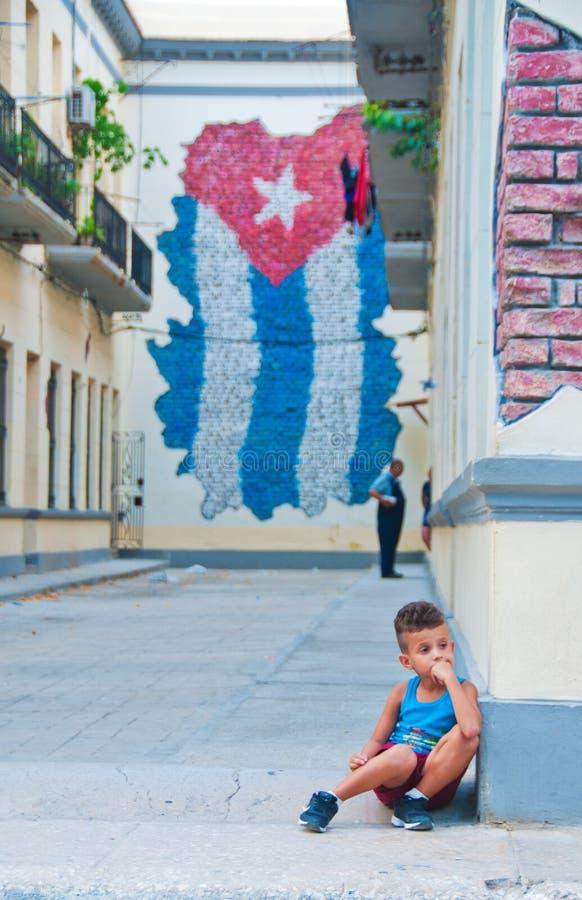 SEPT 21 DE HAVANA, CUBA, 2016: Ideia do assento pensativo do rapaz pequeno fotografia de stock