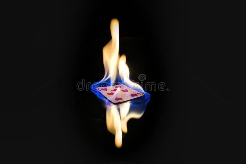 Sept de la carte de jeu de coeurs sur le feu images stock