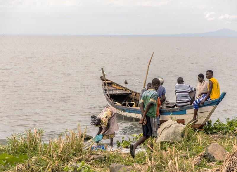 2017 Sept 17: Kaloka strand, Kisumu län, Kenya Män vilar efter ha fiskat för morning's fotografering för bildbyråer