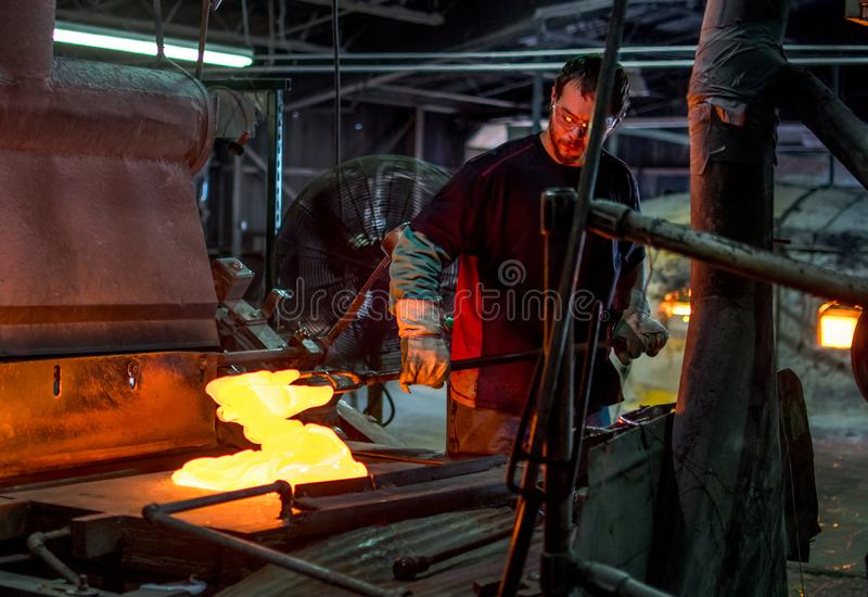Molten glass being mixed and made into stained glass sheets. Sept 27 2019 Kokomo Indiana USA; this glass worker is mixing molten hot glass, which will soon be royalty free stock photo