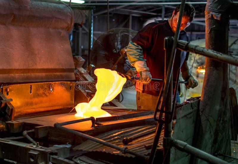 Glass worker mixes molten glass at a glass factory. Sept 27 2019 Kokomo Indiana USA; A talented glass worker mixes molten hot glass, and in this process, creates stock images