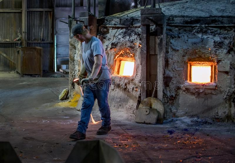 Hot glass and worker in a glass factory. Sept 27 2019 Kokomo Indiana USA; A worker carries a ladle of molten glass, just removed from a very hot kiln, at a royalty free stock photography