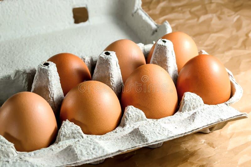 Sept oeufs bruns de poulet dans un emballage de papier de carton sur une table de cuisine Oeufs pour la consommation saine de bre images stock