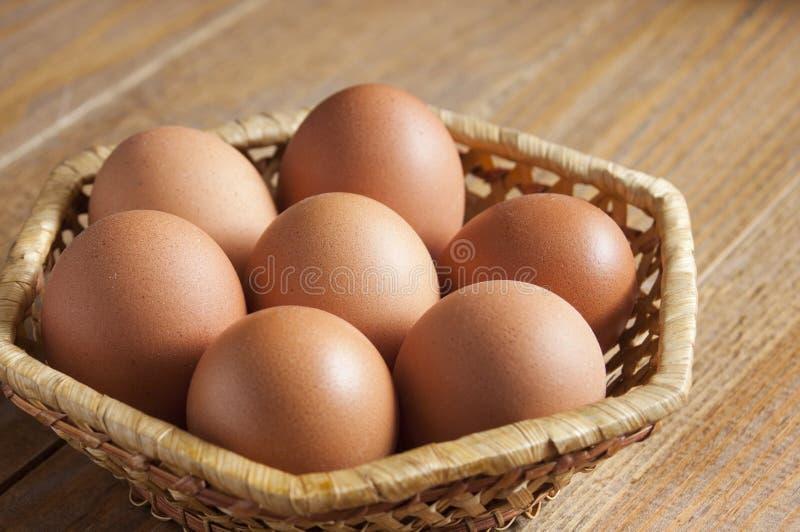 Sept oeufs bruns de poulet s'étendent dans un panier en osier sur une table image stock