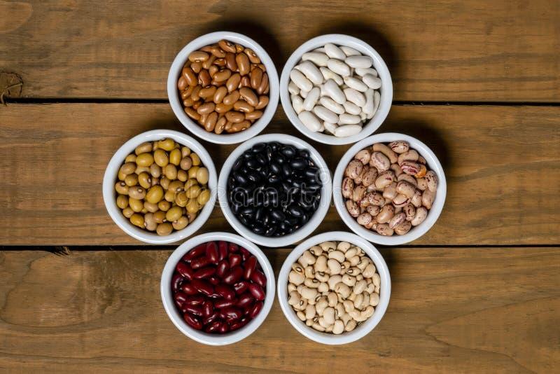 Sept variétés de haricots à l'intérieur du pot blanc sur le fond brun en bois photos stock