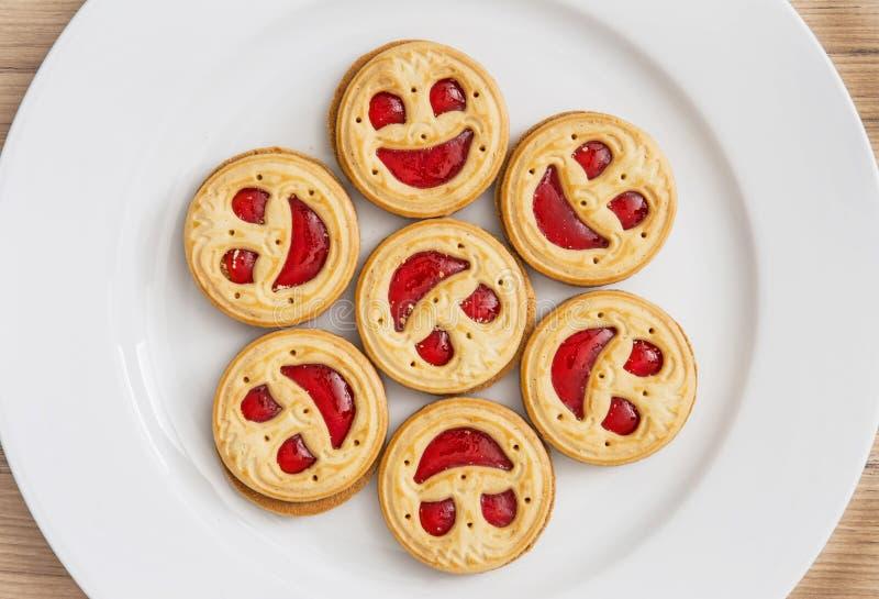 Sept visages de sourire de biscuits ronds du plat blanc images stock
