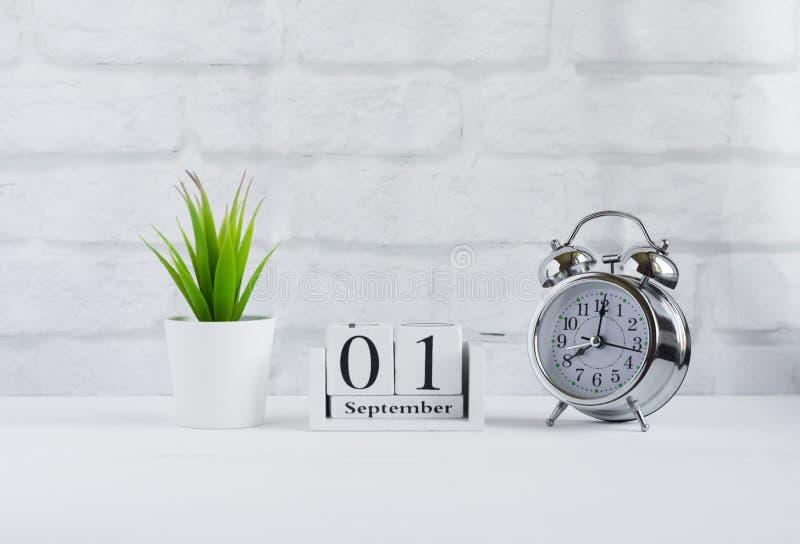 1. September auf einem hölzernen Kalender nahe bei dem Wecker, das Konzept des Beginns des neuen Schuljahres lizenzfreies stockfoto