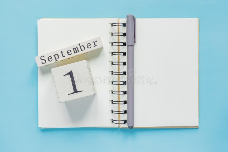 1. September auf einem hölzernen Kalender auf Studienlehrbuch auf blauem Hintergrund Zur?ck zu Schule-Konzept stockfotos