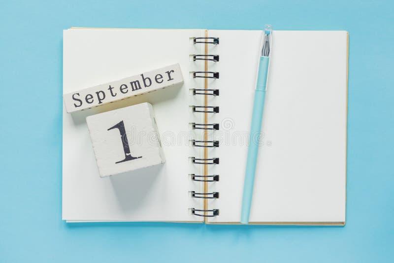 1. September auf einem hölzernen Kalender auf Studienlehrbuch auf blauem Hintergrund Zur?ck zu Schule-Konzept stockbilder