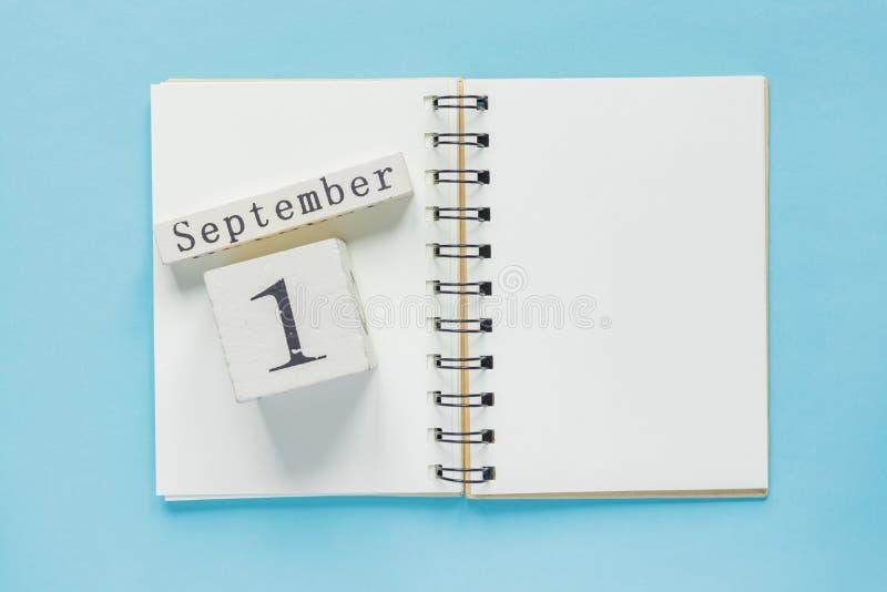 1. September auf einem hölzernen Kalender auf Studienlehrbuch auf blauem Hintergrund Zur?ck zu Schule-Konzept lizenzfreies stockbild