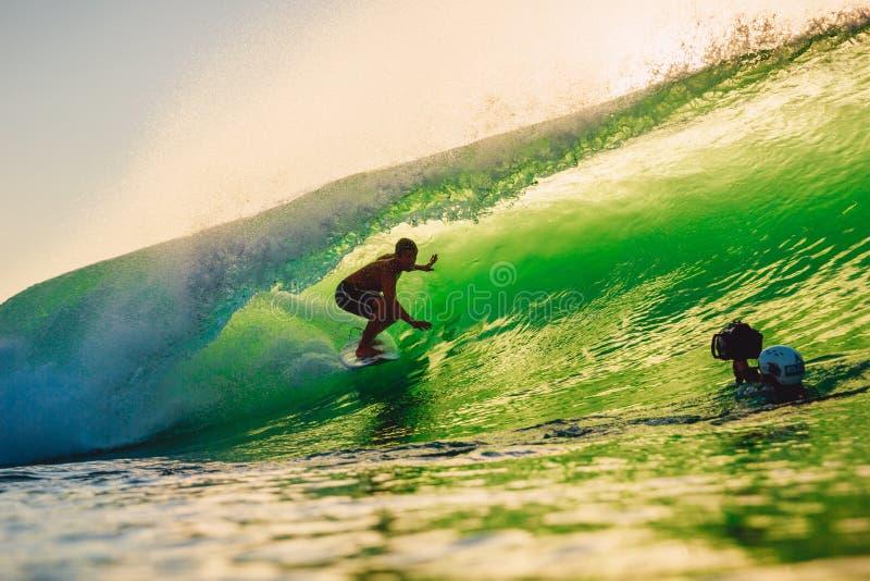 8. September 2018 Bali, Indonesien Surferfahrt auf Fasswelle bei warmem Sonnenuntergang Berufssurfen in Ozean, Bingin-Strand lizenzfreie stockbilder