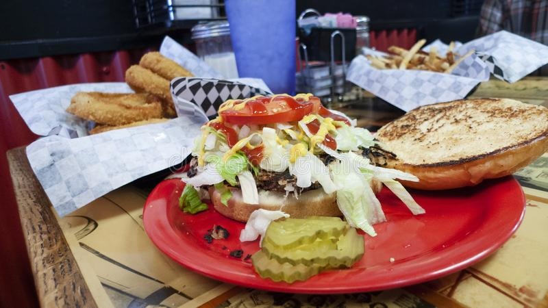 Sid`s Diner, El Reno, Oklahoma, onion rings and a burger. September 10, 2019, a basket of onion rings with ketchup and a huge hamburger with grilled bun, pickles royalty free stock photos