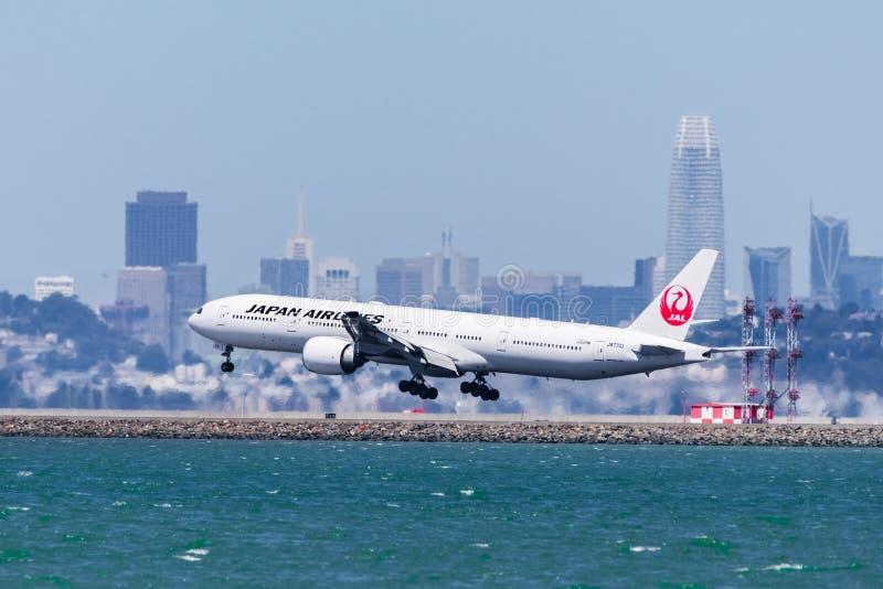 September 1, 2019 Burlingame / CA / USA - Japan Airlines aircraft landing at San Francisco International Airport; Downtown San royalty free stock photos