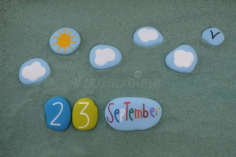 23 September, calendar date composed with multi colored stones over green sand royalty free stock image