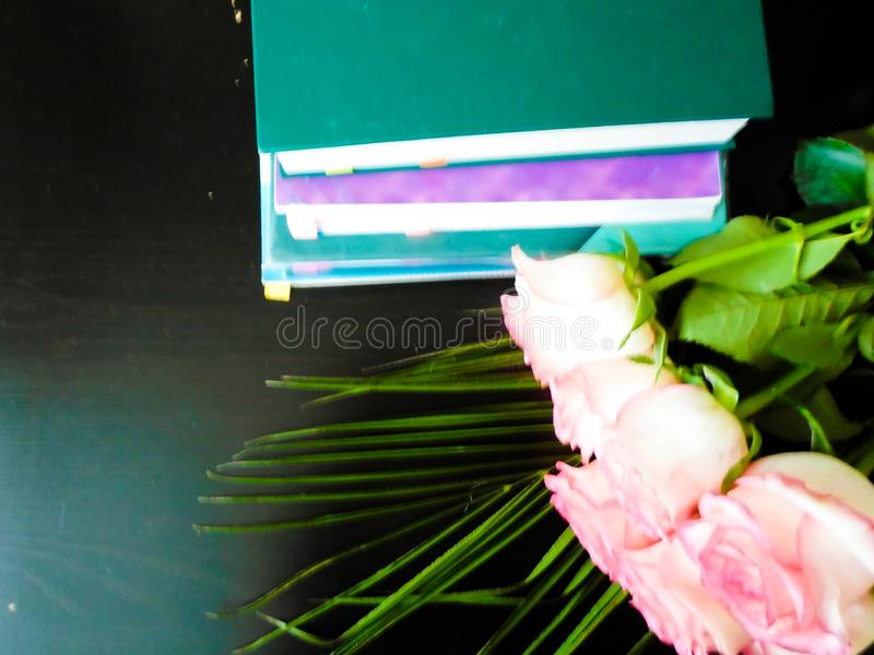September 1 concept, teacher`s day, it`s time to go to school. Books and flowers on a black table. festive mood stock photography