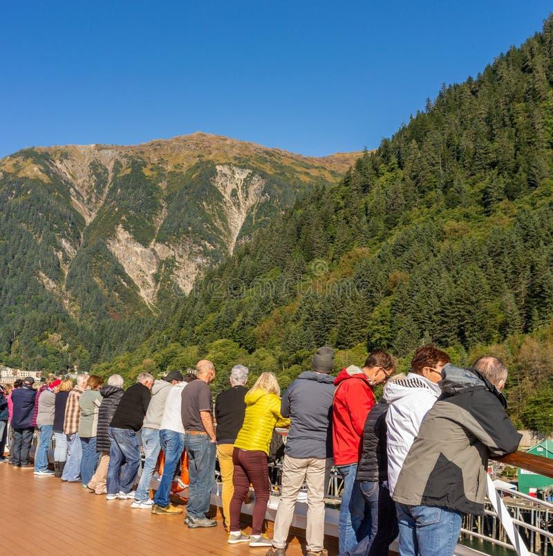 September 14, 2018 - Juneau, AK: Ship passengers peer over railing while docking royalty free stock photos