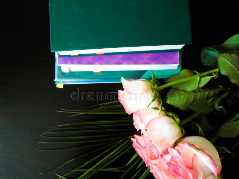 1. September Konzept, der Tag des Lehrers, ist es Zeit zu gehen zu schulen Bücher und Blumen auf einer schwarzen Tabelle Festlich lizenzfreie stockfotografie