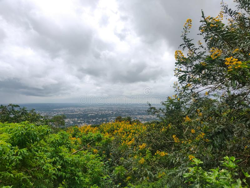 September 8, 2019-Mysore, India: Landscape Arial view of Mysore city through trees and bushes with cloudy sky in the background.  stock photography