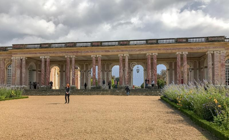 Pink marble terrace at the Grand Trianon, Versailles, France. September 2017: Pink marble terrace under cloudy skies at the Grand Trianon, Versailles, France royalty free stock image