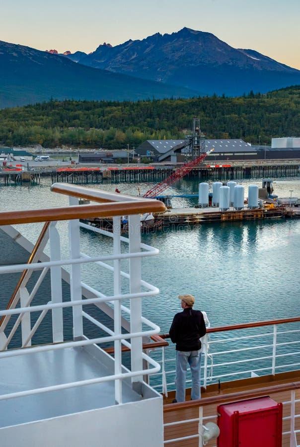 September 15, 2018 - Skagway, AK: Cruise ship passenger overlooking harbour from docking ship at sunrise. stock photo