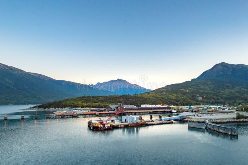 15 september, 2018 - Skagway, AK: Kleine boothaven en industriële dokken bij zonsopgang stock afbeeldingen