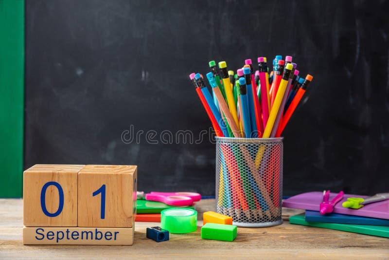 September 1st datum och färgrika skolatillförsel på svart tavlabakgrund royaltyfria bilder