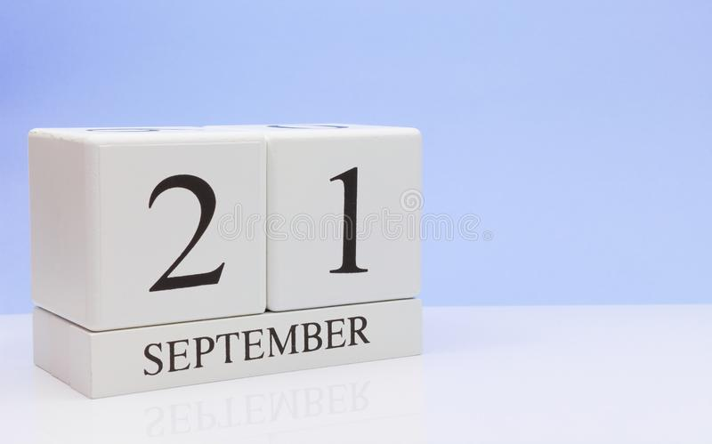 September 21st. Day 21 of month, daily calendar on white table with reflection, with light blue background. Autumn time, empty stock image