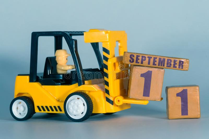 September 11th. Day 11 of month, Construction or warehouse calendar. Yellow toy forklift load wood cubes with date. Work planning. And time management. autumn stock photography
