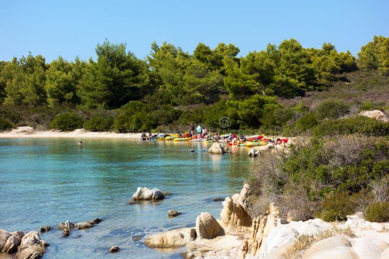 September 9th 2017 - den Diaporos ön, Sithonia, Grekland - en grupp människor med deras kanoter i en avskild strand royaltyfria bilder