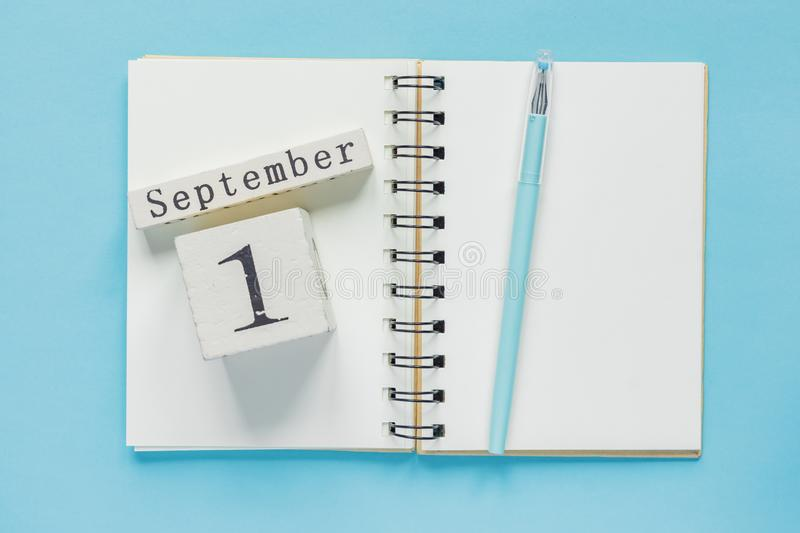 September 1 on a wooden calendar on study textbook on  blue background. Back to school concept.  stock images