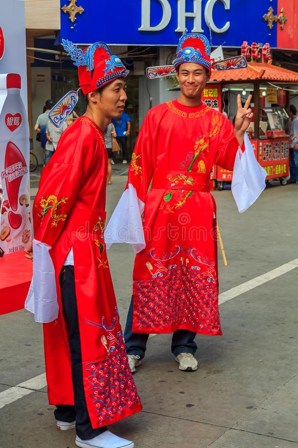 Unidentified people in traditional outfits a busy shopping stree. September 14, 2013 -Xiamen, China: Unidentified people in traditional outfits a busy shopping stock images