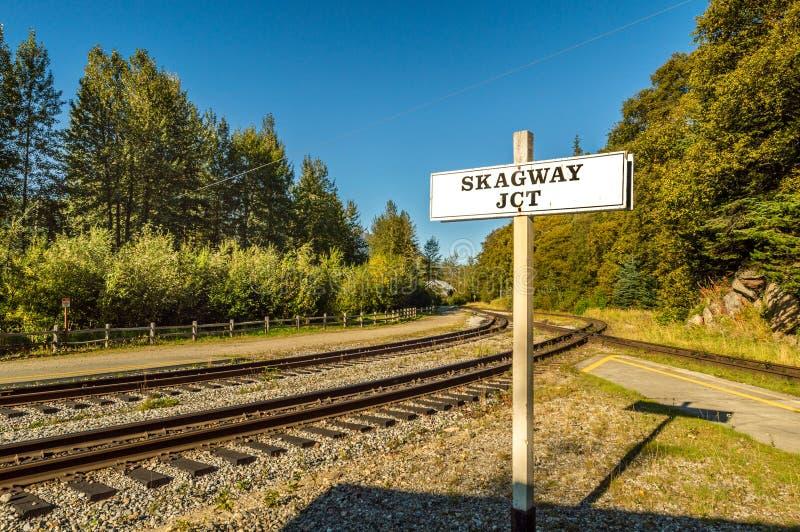 15 septembre 2018 - Skagway, AK : Poteau indicateur de jonction de Skagway suivant le passage et la ligne blancs de rail d'itinér photographie stock libre de droits