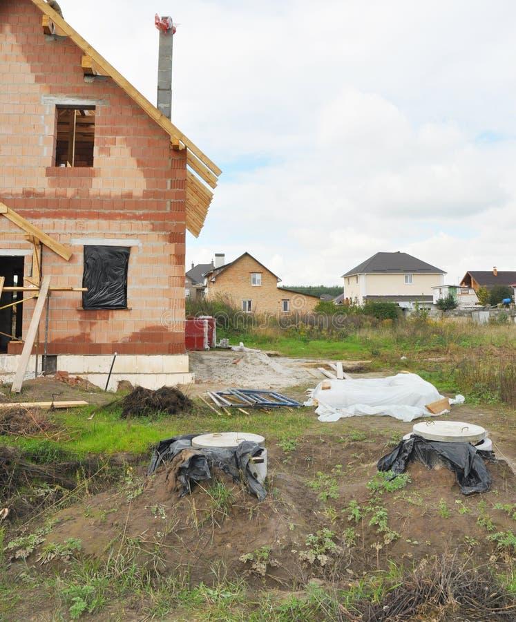 Septische mangatdekking en concrete tanks die in de huisbouwwerf installeren stock foto