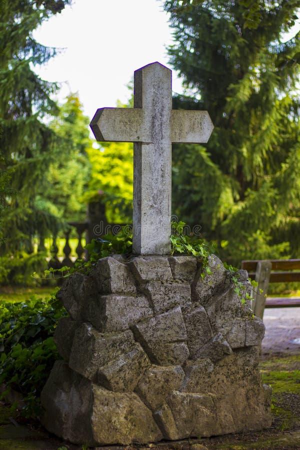 Sepultura transversal e de pedra na Croácia no parque foto de stock