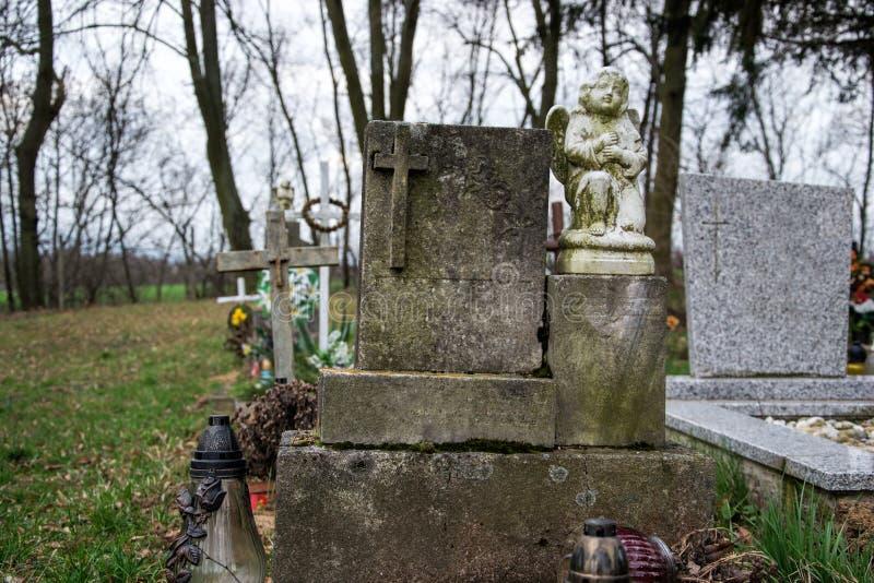 Sepulturas, lápides e crucifixos no cemitério tradicional Estátua de um anjo na pedra velha do túmulo no cemitério Todo o Saints& fotografia de stock