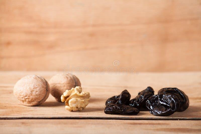 Seque a ameixa seca e a noz na mesa de madeira fotos de stock