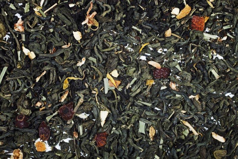 Seque el té verde con los pétalos de la flor y de la fruta imagenes de archivo