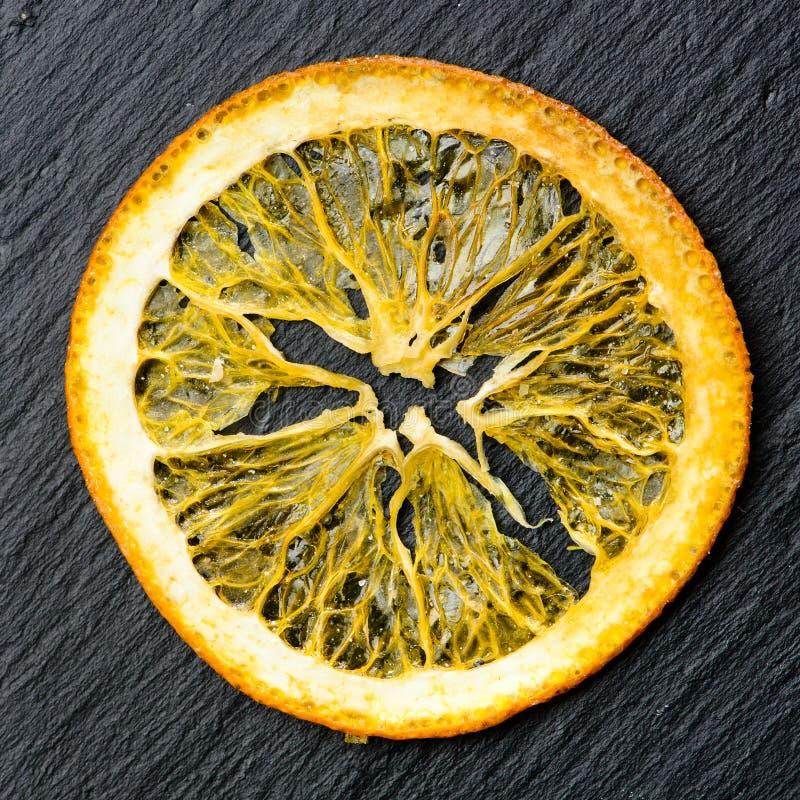 Seque a fatia amarela de limão no fundo escuro foto de stock
