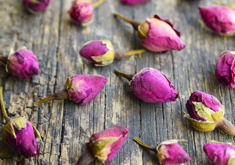 Seque las flores color de rosa de los brotes en la tabla de madera vieja Ingrediente asiático para la infusión de hierbas del aro foto de archivo libre de regalías